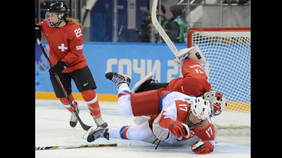 Russian forward Yekaterina Smolentseva tumbles over Swiss goalie Florence Schelling during the women's hockey game on February 15.