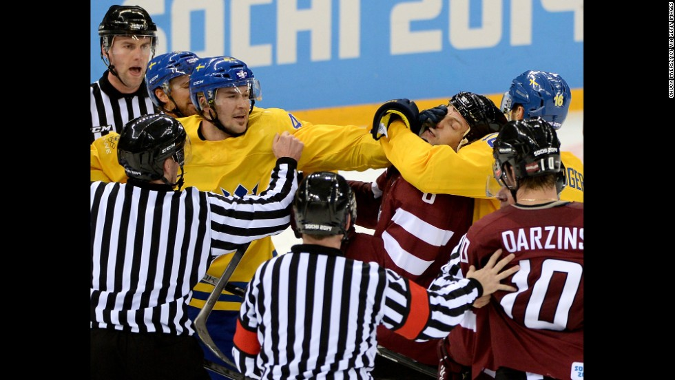Tempers flare late in the third period as Swedish hockey forward Jimmie Ericsson, left, grabs the face of Latvian defenseman Sandis Ozolinsh on February 15.