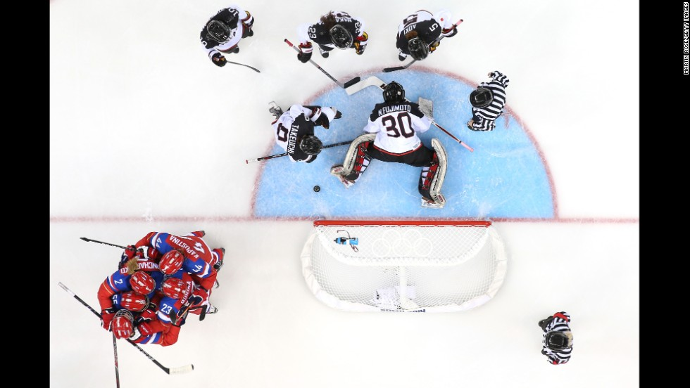 The women's hockey team from Russia, in red, celebrates a goal against Japan on February 16.