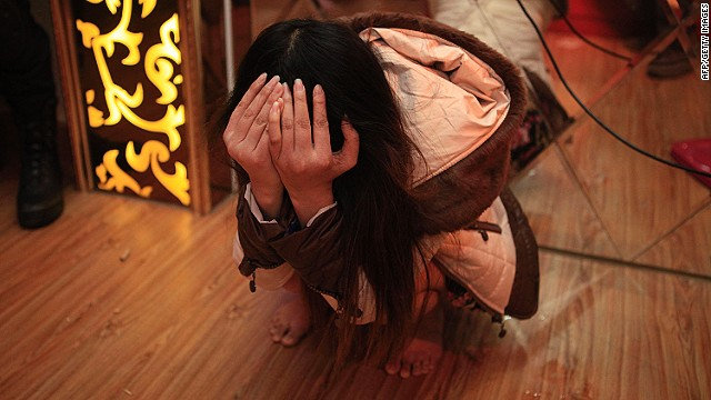 An alleged sex worker covers her face after being detained in Dongguan, China, on February 9, 2014