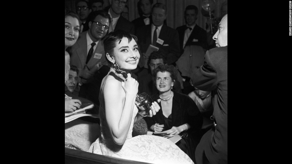 "Audrey Hepburn is surrounded by reporters as she holds her best actress Oscar for ""Roman Holiday."""