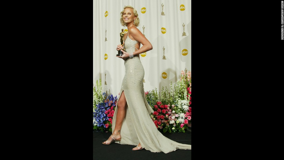 "Charlize Theron poses with her Oscar after winning for the film ""Monster."""
