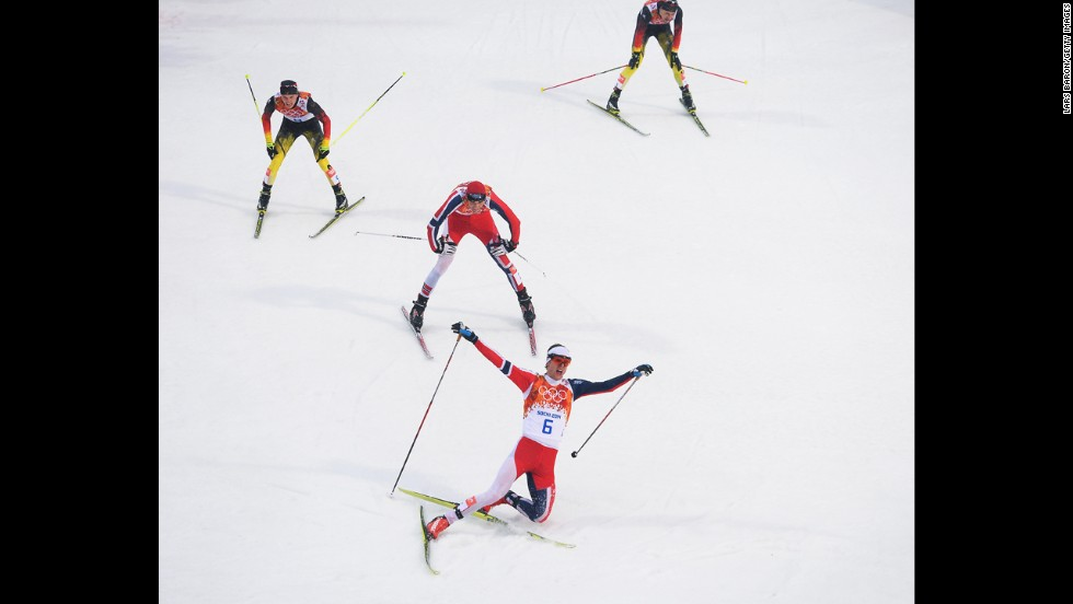 Joergen Graabak of Norway celebrates as he crosses the line to win the gold medal in the large hill Nordic combined event February 18.