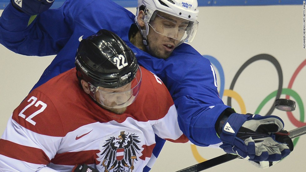 Slovenia's David Rodman, right, fights for the puck with Austria's Thomas Pock during a hockey game February 18.