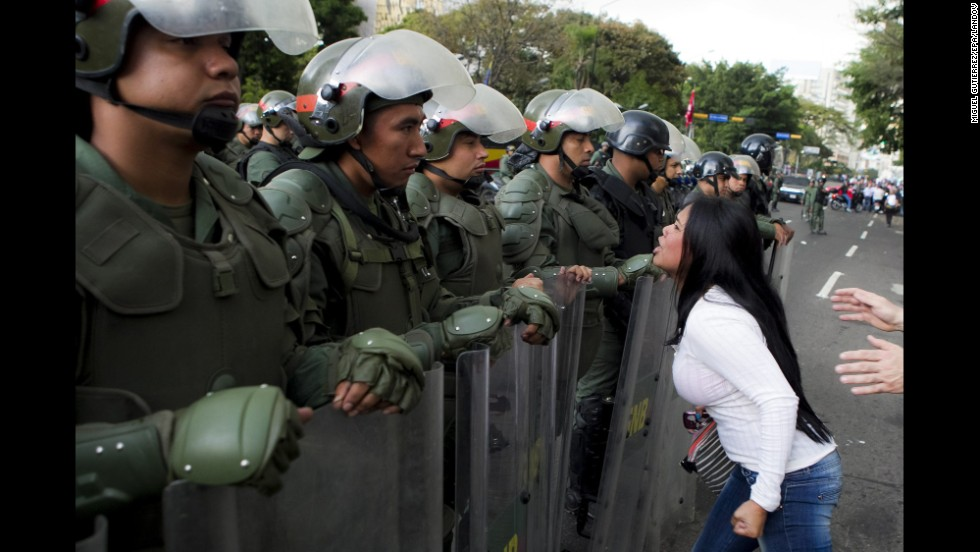 A young woman argues with members of the Venezuelan National Guard during an anti-government protest in Caracas on Monday, February 17.