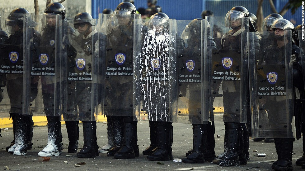 Riot police stand during clashes in Caracas on February 15.