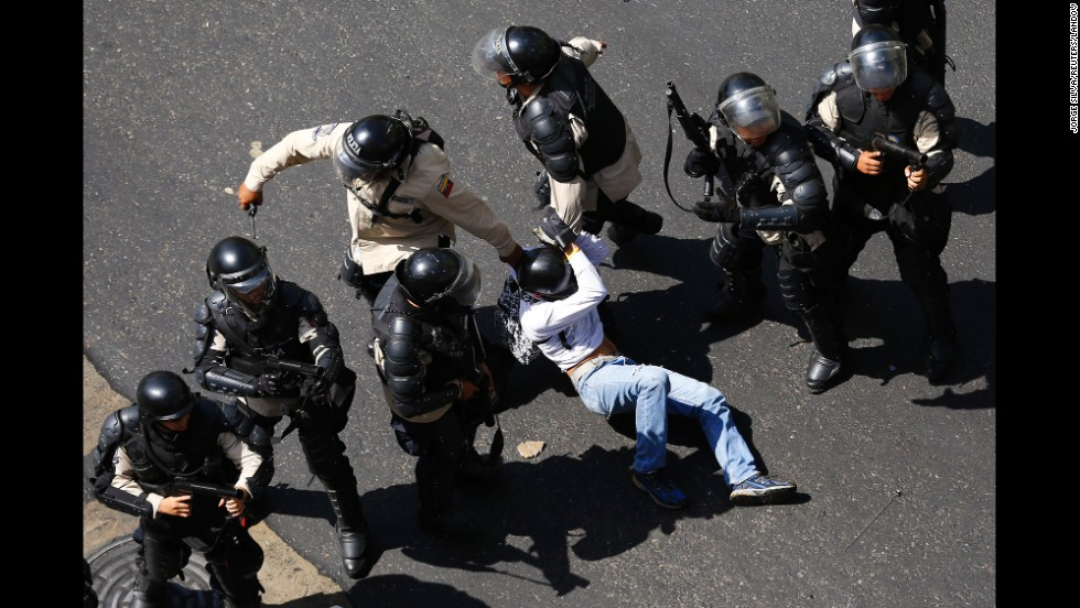 A demonstrator is detained after jumping over a riot police line in Caracas on February 12.