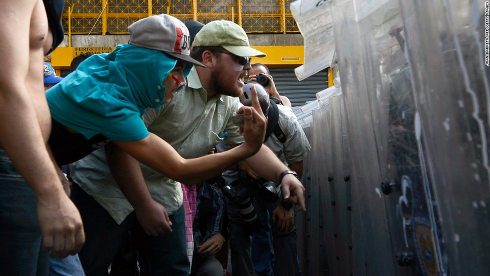 Protesters confront riot police in Caracas on February 12.
