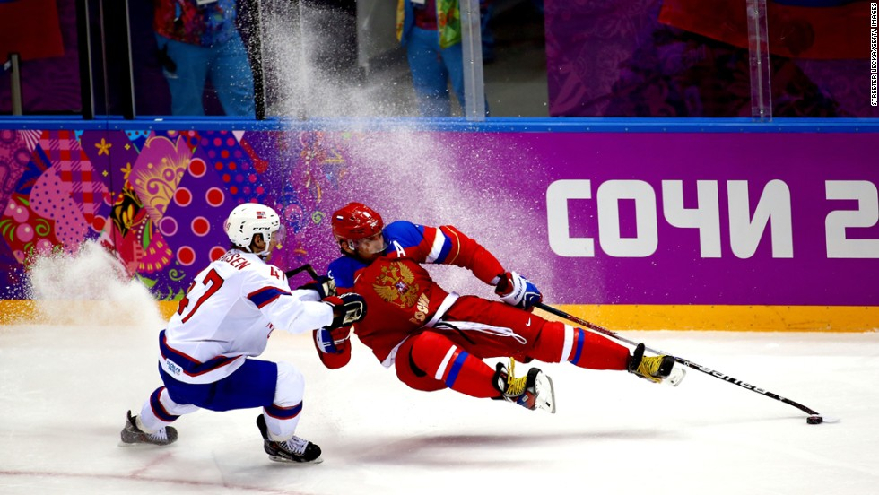 Russian hockey player Alexander Ovechkin, right, falls while playing against Norway's Alexander Bonsaksen during an Olympic game Tuesday, February 18.
