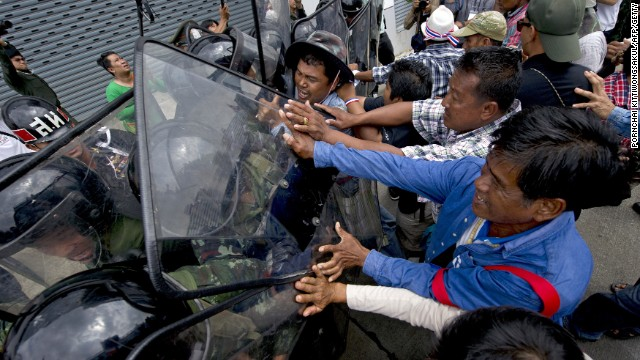 Thai farmers battle with soldiers as they protest the government's repeatedly delayed payments for rice submitted to the pledging scheme at the government's temporary office in Bangkok on February 17, 2014. Thai opposition demonstrators besieged government offices on February 17, including a compound that has been used as a temporary headquarters by Prime Minister Yingluck Shinawatra, in defiance of authorities who have vowed to reclaim key state buildings. AFP PHOTO / PORNCHAI KITTIWONGSAKUL (Photo credit should read PORNCHAI KITTIWONGSAKUL/AFP/Getty Images)