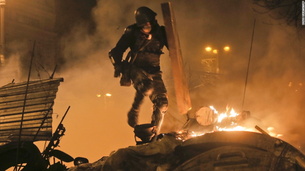 A protester runs during clashes with police in Kiev on February 18.