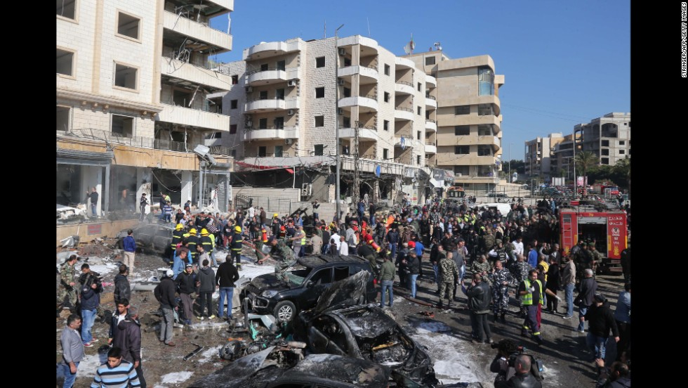 Emergency personnel and civilians inspect the site of one of the explosions. The al Qaeda-linked militant group Abdullah Azzam Brigades claimed responsibility for the attacks.