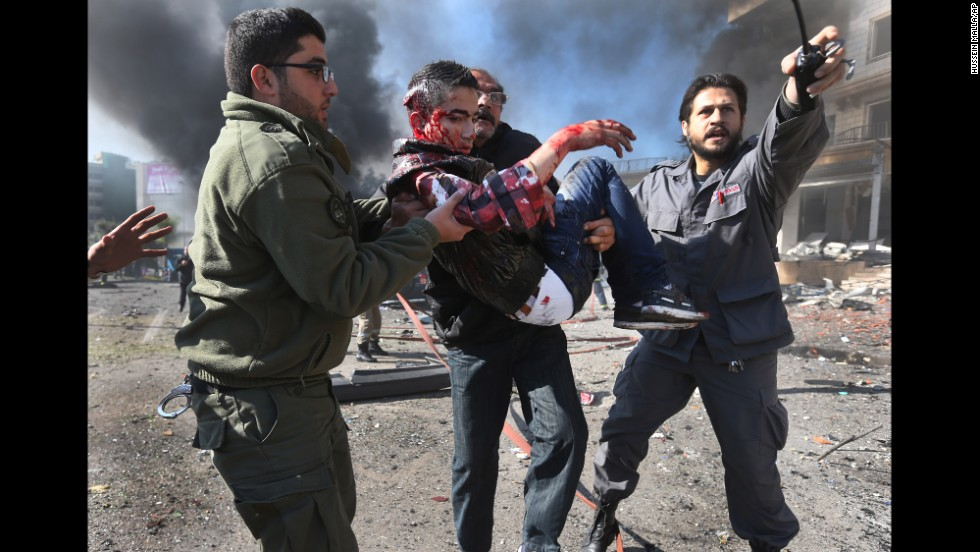 Men carry one of the injured after the blast in Beirut on February 19. The group with al Qaeda ties has warned of more attacks unless Iranian-backed Shiite militia Hezbollah stops sending fighters to support Syrian government forces.