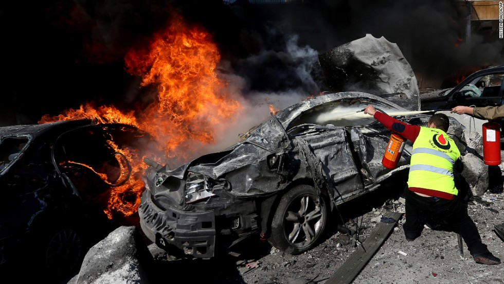 A civil defense worker tries to extinguish flames from a car in Beirut on February 19.