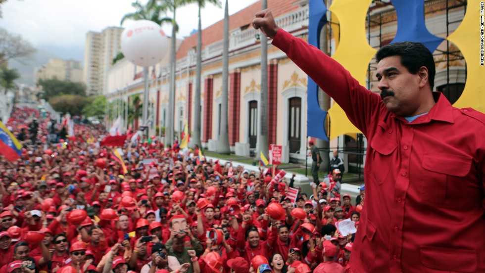 President Maduro raises his fist during a rally in Caracas on February 18, in this photo released by the Venezuelan government. Maduro and his supporters have blamed the opposition for causing the very problems it protests.