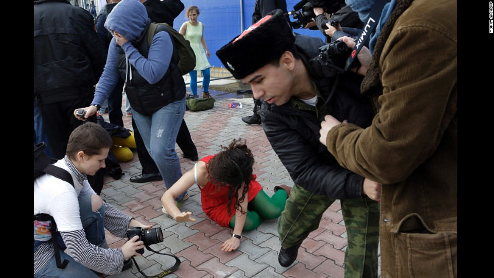 "A member of Pussy Riot lies on the ground February 19. The band <a href=""http://www.cnn.com/2014/02/06/world/gallery/pussy-riot/index.html"">has been highly critical</a> of Russian President Vladimir Putin and his policies, and Alyokhina and Tolokonnikova were even imprisoned for a 2012 ""punk prayer"" performance at a Russian Orthodox cathedral."