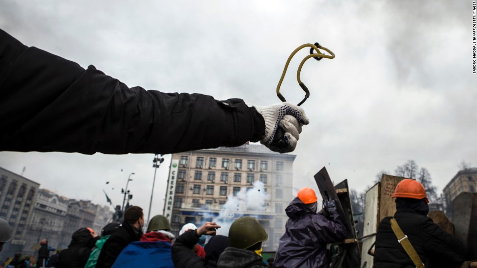 A protester uses a slingshot to throw a rock at riot police February 19 in Kiev.