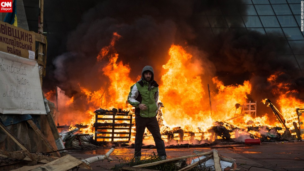"A Ukrainian protester stands in front of the burning Euromaidan protest camp in Kiev on Wednesday February 18. Protesters set up tents in the square in December, says iReporter and American journalist <a href=""http://ireport.cnn.com/docs/DOC-1087484"">Chris Collison</a>."