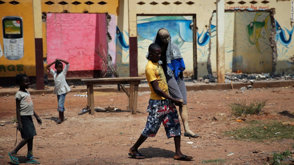 "A man carries a charred mannequin wearing a Muslim veil in front of looted stores, past a convoy of more than 100 vehicles of Muslims fleeing Bangui, Central African Republic, on February 14. The United Nations -- estimating more than half the country's population is affected by the worsening humanitarian crisis -- has said <a href=""http://www.cnn.com/2014/02/14/world/africa/central-african-republic-france-troops/index.html"">it fears genocide brewing</a>."