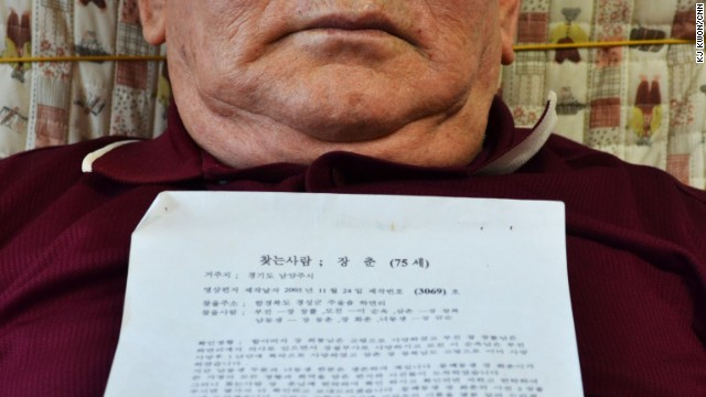 Jang Chun holds a letter and several photos of his family in North Korea through the Red Cross.