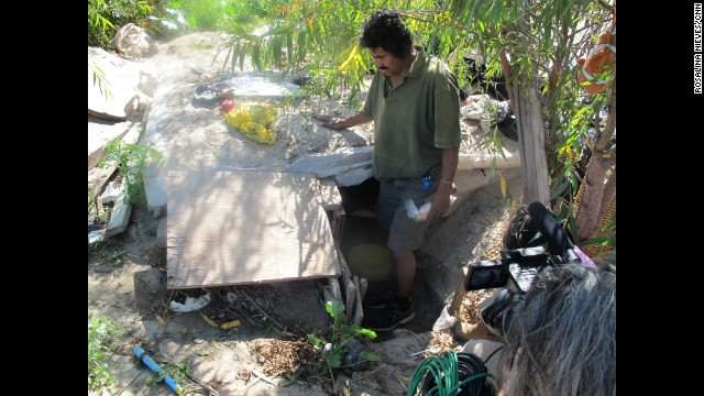 Fernando Miranda shows the underground hut he covered with leftover plywood.
