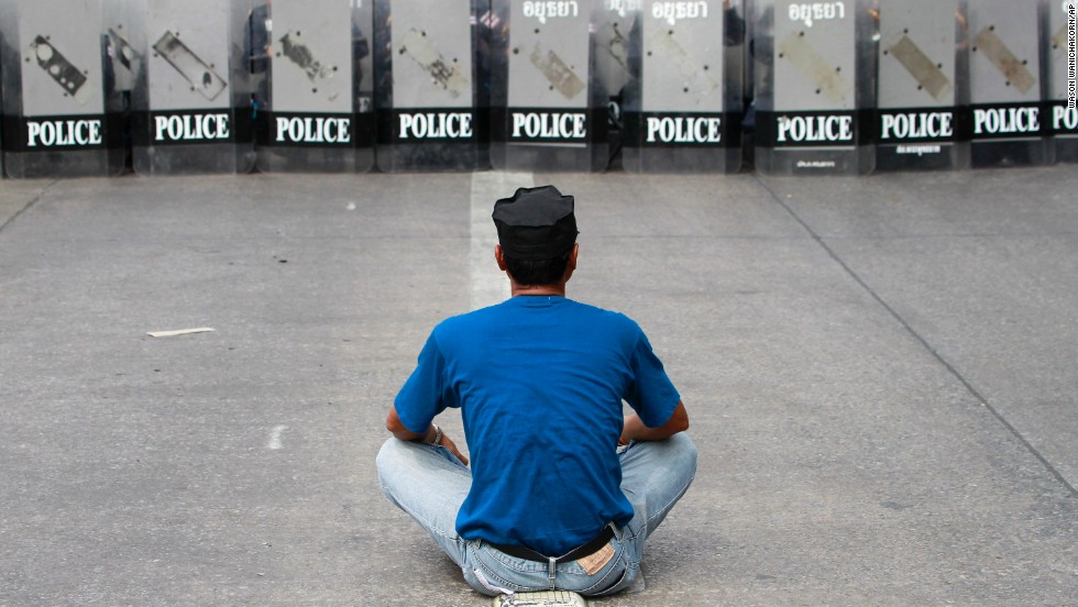 A demonstrator sits in front of a row of riot police during an operation to reclaim government offices occupied by protesters in Bangkok on February 14. The attempted evictions led to a flare-up of violence after a period of relative calm.
