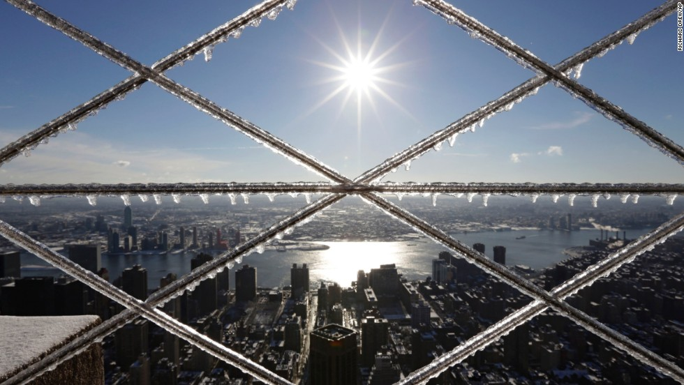 "The morning sun is framed by ice crusted on a barrier on the observation deck of New York's Empire State Building on February 14. Commuters faced slick roads after <a href=""http://www.cnn.com/2014/02/12/us/gallery/winter-storm-0212/index.html"">a winter storm brought snow and ice</a> to the East Coast."