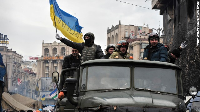 Anti-government protesters, one holding the Ukrainian national flag, drive a military vehicle at the Independence square in central Kiev on February 22, 2014. Ukraine's leader and opposition on Friday signed a deal to end the splintered country's worst crisis since independence after three days of carnage left nearly 100 protesters dead. President Viktor Yanukovych's dramatic decision to hold early elections and form a new unity government was met with caution by the tens of thousands gathered on central Kiev's main square for a protest that began exactly three months earlier. .AFP PHOTO/ LOUISA GOULIAMAKI (Photo credit should read LOUISA GOULIAMAKI/AFP/Getty Images)