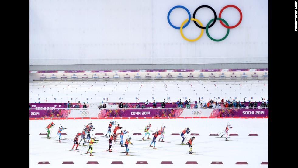 Skiers pass the Olympic rings as they compete during the men's 4x7.5-kilometer cross country relay on February 22.