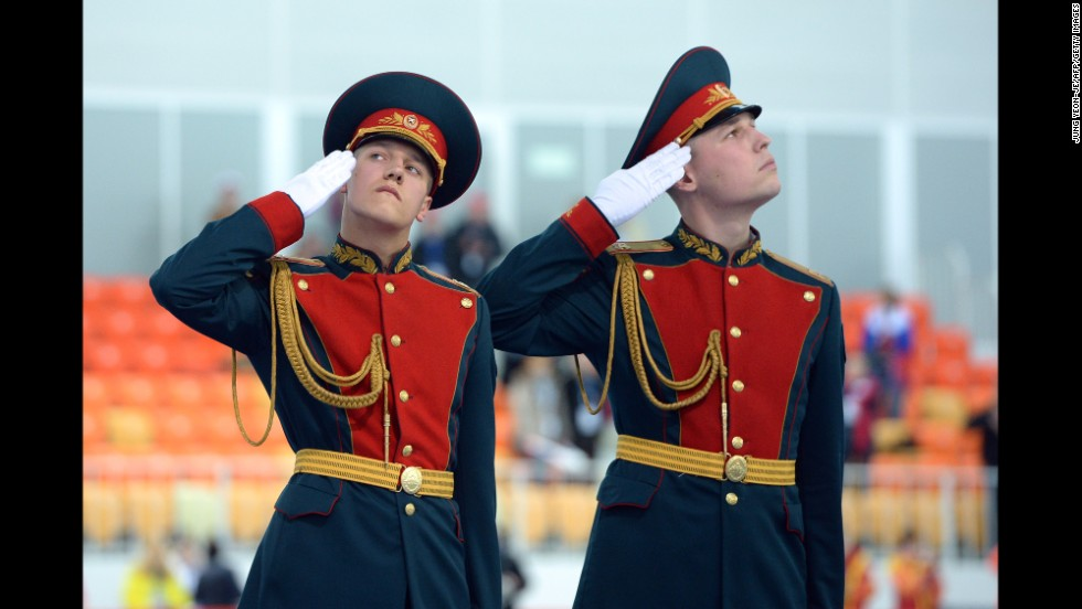 Russian honor guards salute on February 22, during the ladies' speed skating team pursuit medal ceremony.
