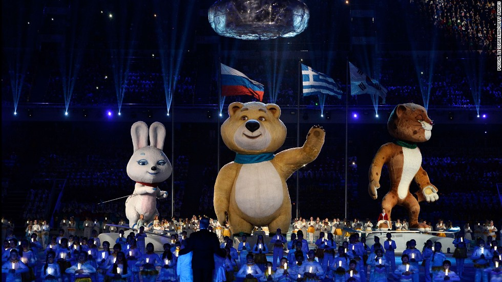 Olympic mascots the Hare, the Polar Bear and the Leopard stand by the extinguished Olympic flame.