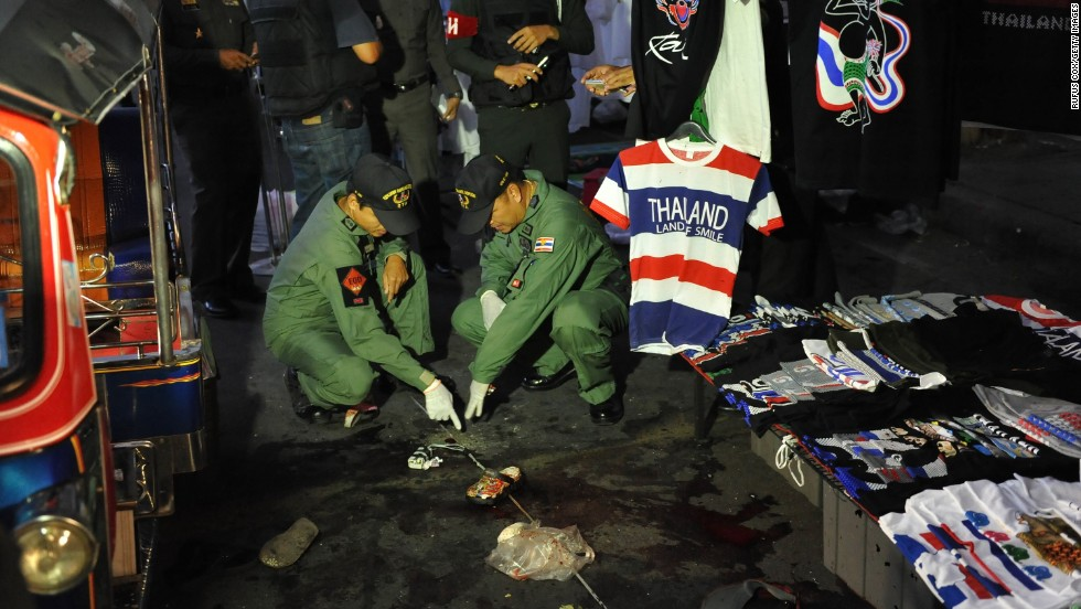 A bomb squad examines the scene of an explosion at an anti-government rally in Bangkok on February 23. Two children and a woman were killed and more than 20 injured outside a shopping mall. Protesters have been calling for the ouster of Prime Minister Yingluck Shinawatra, whom they allege is a puppet of her billionaire brother, the deposed, exiled former Prime Minister Thaksin Shinawatra.