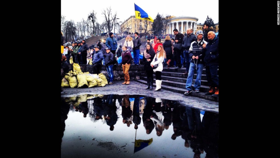 "KIEV, UKRAINE:  Ukrainians are reflected in a puddle as they gather to mourn the dead in Maidan Square on February 23, after protesters succeeded in forcing President Viktor Yanukovich out of office.  Photo by CNN's Christian Streib.  Follow Christian on Instagram at <a href=""http://instagram.com/christianstreibcnn"" target=""_blank"">instagram.com/christianstreibcnn</a>."