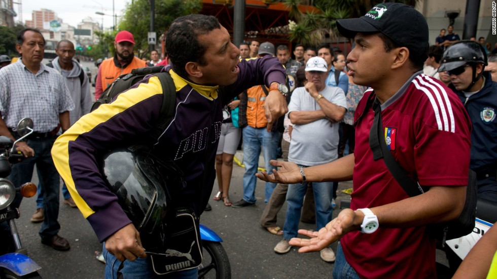A motorcyclist, left, argues with demonstrators blocking a highway in Caracas on February 24.
