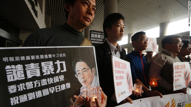 Protesters hold a picture of former Ming Pao editor Kevin Lau outside a hospital in Hong Kong.