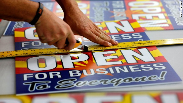 "Tom Cushing, a production expert at Fast Signs in Phoenix, Arizona, cuts down a sheet of anti-Senate Bill 1062 signs that read ""Open For Business To Everyone"" on Wednesday before Gov. Jan Brewer vetoed the controversial measure."