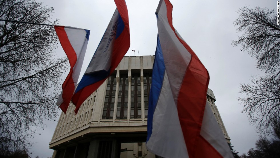 Pro-Russia demonstrators wave Russian and Crimean flags in front of a local government building in Simferopol on February 27.