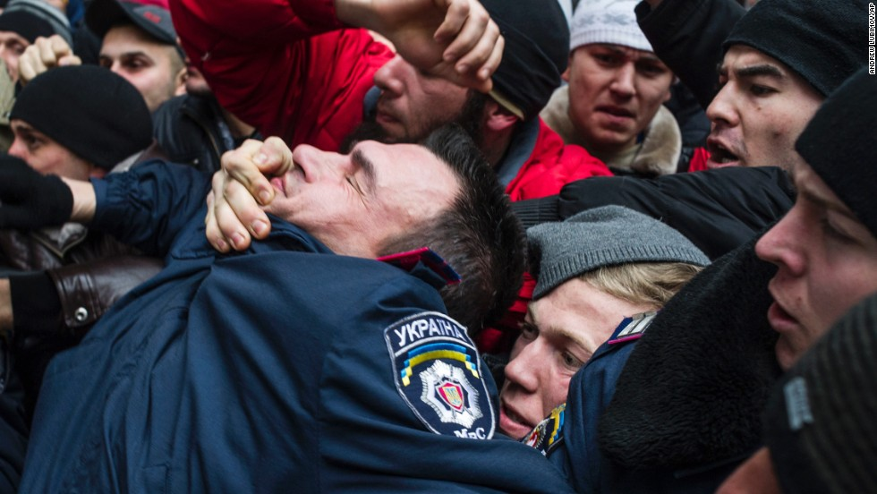 A police officer gets pulled into a crowd of Crimean Tatars in Simferopol on February 26. The Tatars, an ethnic minority group deported during the Stalin era, rallied in support of Ukraine's interim government.