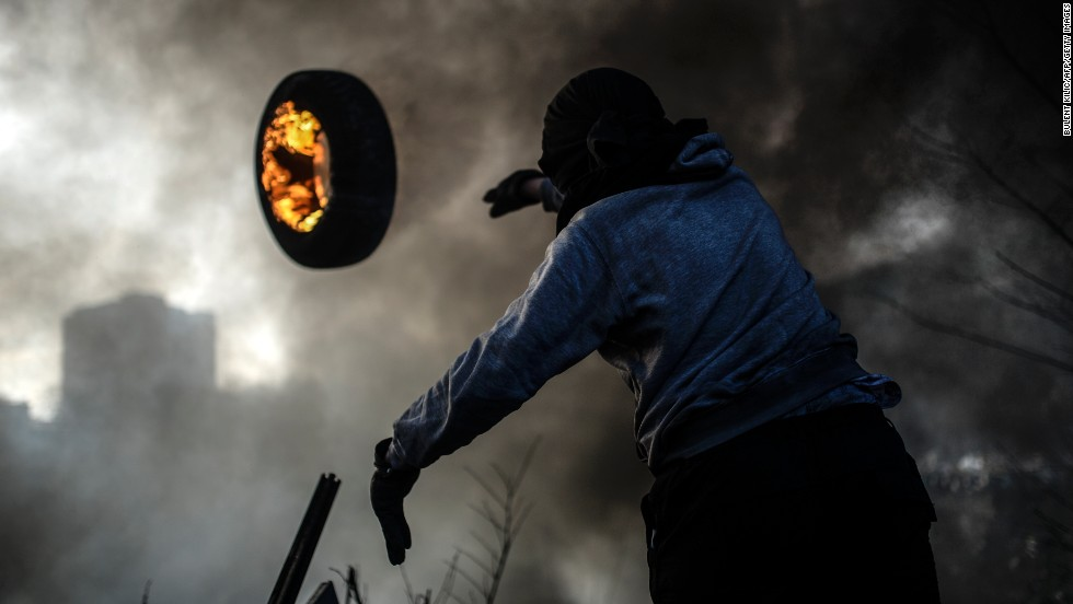 An anti-government demonstrator throws a burning tire as he builds a barricade Friday, February 21, at Independence Square in Kiev, Ukraine.
