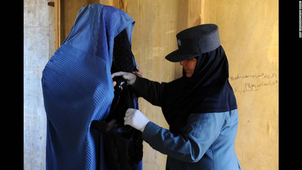 An Afghan policewoman searches a burqa-clad resident at a voter registration center in Herat province on Wednesday, February 26. Afghanistan is due to hold elections in April.