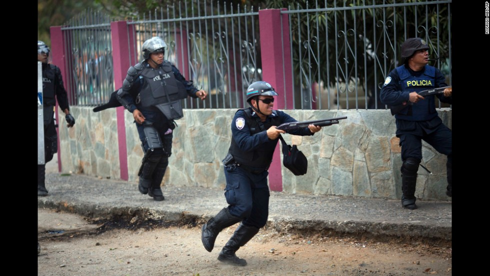 A policeman fires his shotgun to disperse protesters in Valencia on February 26.