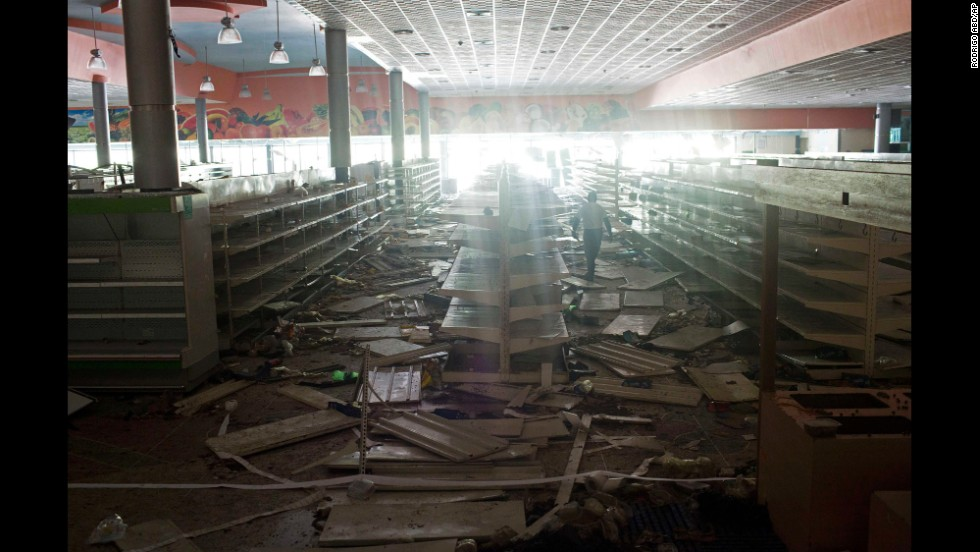 An employee of a supermarket in Maracay, Venezuela, inspects the damage done by looters on February 26.