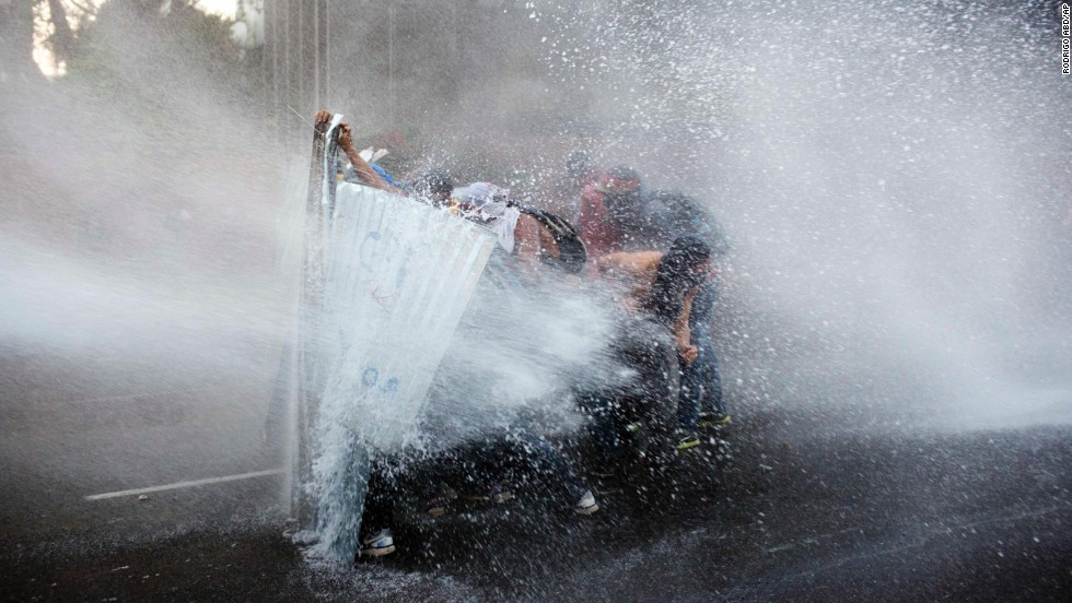 Protesters take cover from a police water cannon in Caracas on February 28.