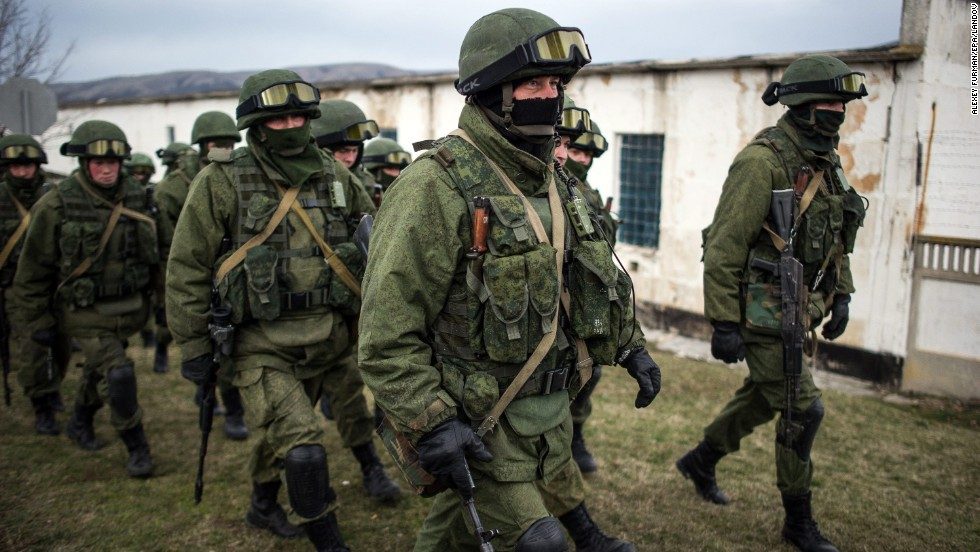 Armed men in military uniform walk outside a Ukrainian military unit near Simferopol on Sunday, March 2. Hundreds of armed men in trucks and armored vehicles surrounded the Ukrainian base Sunday in Crimea, blocking its soldiers from leaving.