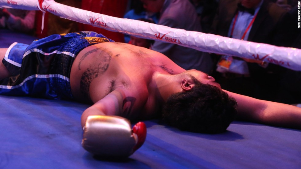 Thai boxer Benz lies on the canvas Friday, February 28, after being knocked out by Chinese boxer Zhang Junlong during a World Boxing Federation match in Qingdao, China.