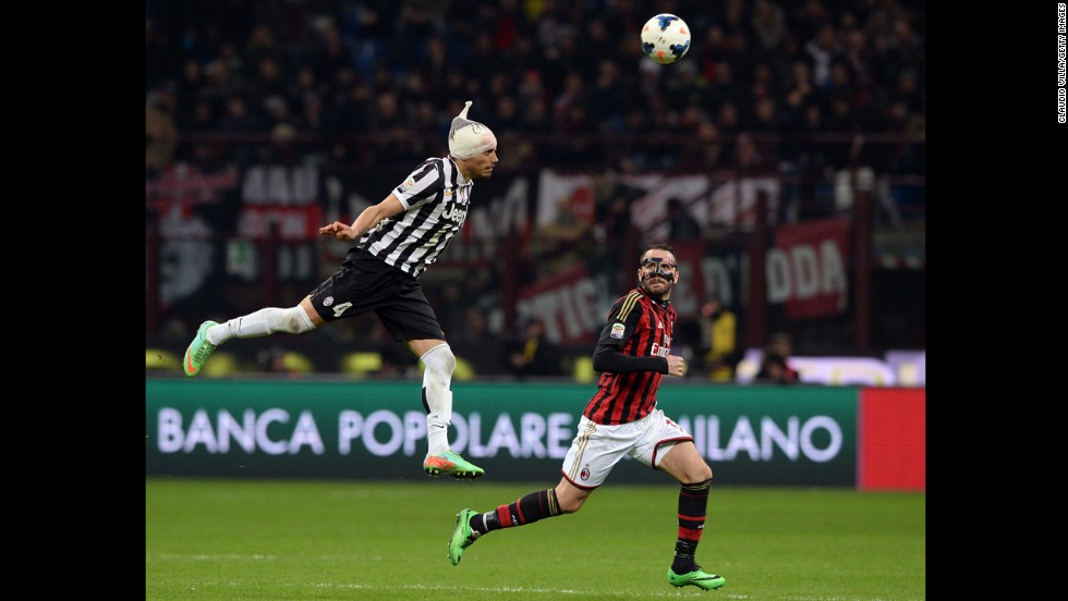 Giampaolo Pazzini of AC Milan looks back as Martin Caceres of Juventus leaps for the ball during a Serie A match in Milan, Italy, on Sunday, March 2.