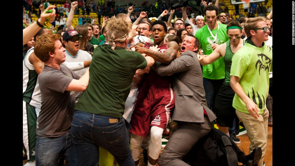 New Mexico State's Daniel Mullings, center, is caught up in a brawl involving players and fans after the game at Utah Valley on Thursday, February 28. The melee started after New Mexico State guard K.C. Ross-Miller hurled the ball at Utah Valley's Holton Hunsaker seconds after Utah Valley's 66-61 overtime victory.
