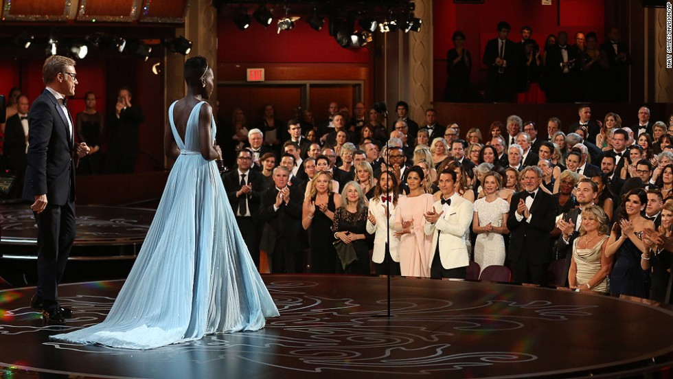 "MARCH 3 - LOS ANGELES, UNITED STATES: Lupita Nyong'o receives a standing ovation as she accepts the award for best actress in a supporting role for <a href=""http://cnn.com/2014/03/02/showbiz/movies/oscars-2014/index.html?hpt=hp_c3"">""12 Years a Slave""</a> during the Oscars at the Dolby Theatre on March 2. The drama was named best picture at the 86th Academy Awards."
