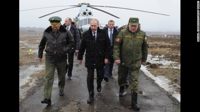 Russia's President Vladimir Putin, center, and Defense Minister Sergei Shoigu, left, arrive to watch a military exercise at the Kirillovsky firing ground in the Leningrad region, on March 3, 2014.