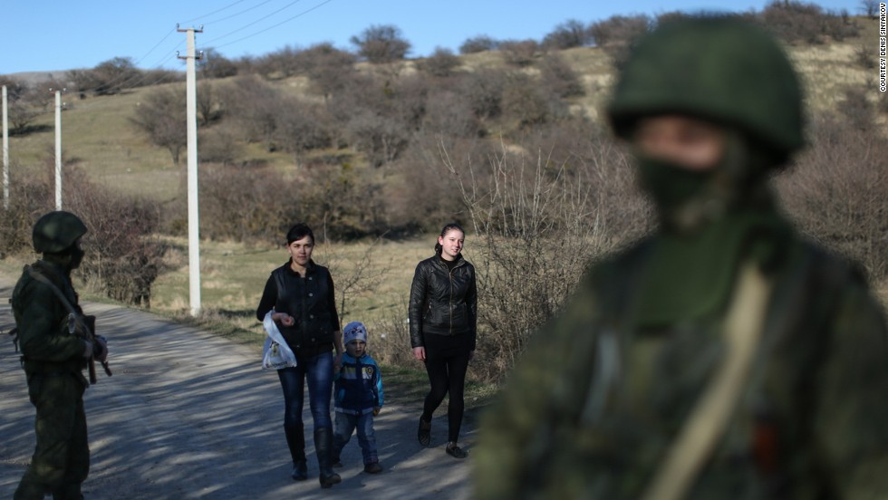 Wives of Ukrainian soldiers walk past Russian soldiers to visit their husbands guarding a military base in Perevalne on March 3.
